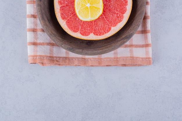 Toranja madura fresca fatiada e limão em uma tigela de madeira.