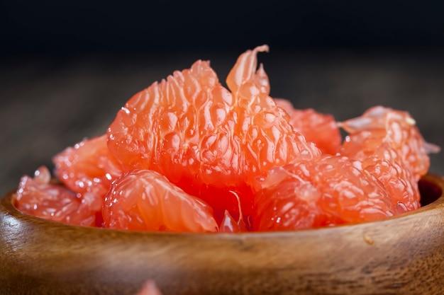 Toranja vermelha descascada dividida em fatias durante o cozimento, toranja cítrica suculenta