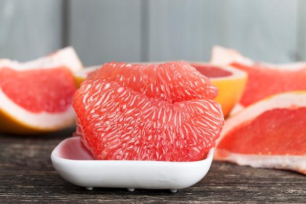 Toranja vermelha descascada e quebrada em fatias e fibras, close de suculentas frutas cítricas em uma tigela branca, preparando uma sobremesa