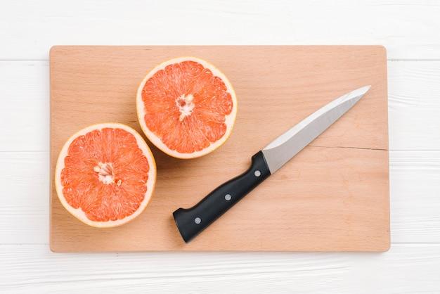 Toranjas cortadas ao meio com a faca afiada na placa de desbastamento de madeira sobre a mesa branca