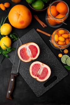 Toranjas fatiadas e laranja com outras frutas cítricas na vista superior de superfície preta