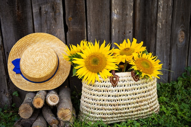 Toras, chapéu, um buquê de girassóis em um saco de palha estão de pé perto de uma casa de madeira.