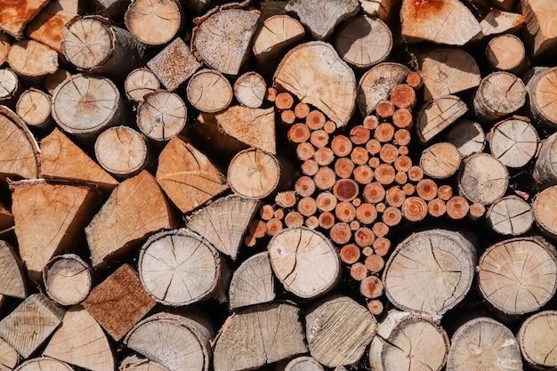 Toras de pilha de madeira dispostas e em forma de estrela em uma parede.