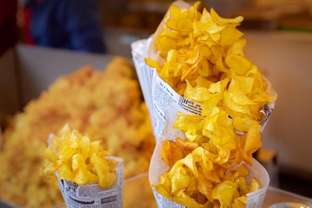 Torção de papel com batatas fritas no mercado de comida de rua.