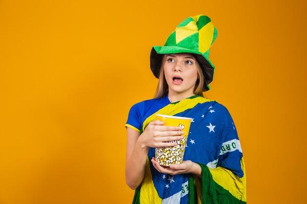 Torcedor brasileiro com pipoca para assistir ao jogo. conceito de entretenimento e esporte