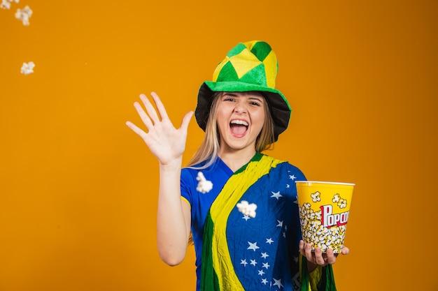 Torcedor brasileiro com pipoca para assistir ao jogo. conceito de entretenimento, esporte e patriotismo
