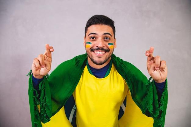 Torcedor brasileiro com uma bandeira nas costas torcendo com os dedos cruzados pela vitória do brasil