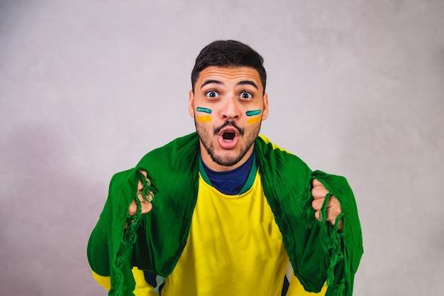 Torcedor brasileiro com uma bandeira nas costas torcendo pela vitória do brasil