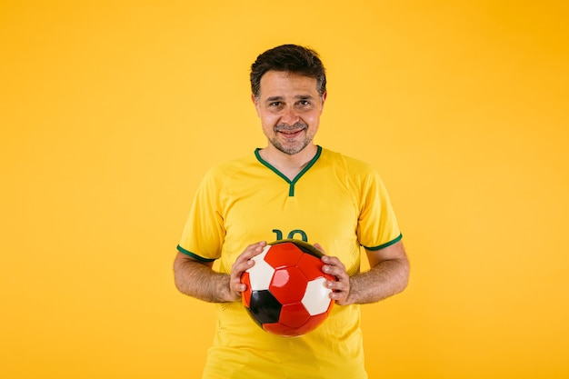 Torcedor brasileiro de futebol com camisa amarela e bola retrô nas mãos