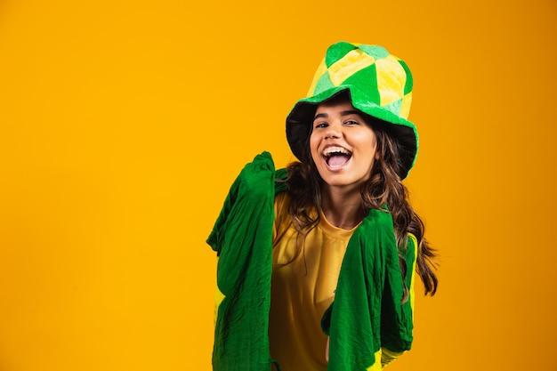 Torcedor brasileiro. fã da mulher brasileira comemorando no futebol ou jogo de futebol em fundo amarelo. cores do brasil.