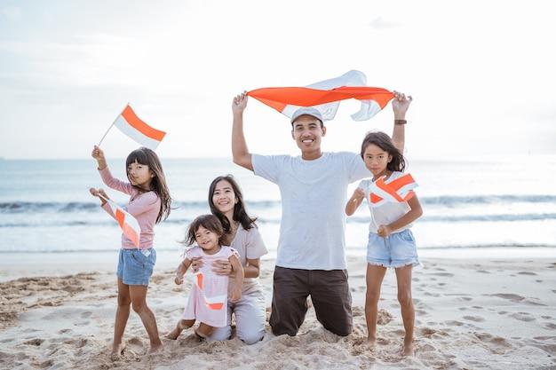 Torcedor da família indonésio empolgado com bandeira da indonésia na praia juntos