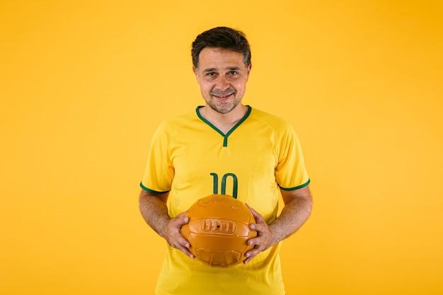Torcedor de futebol com camisa amarela e uma bola retrô nas mãos
