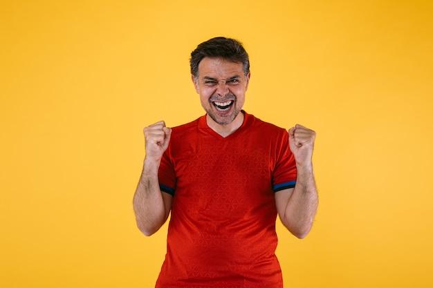 Torcedor de futebol em camisa vermelha aperta os braços com entusiasmo e grita