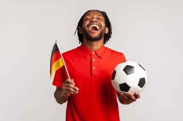 Torcedor de futebol masculino sinceramente regozijando-se, apoiando o time favorito segurando a bola e a bandeira alemã