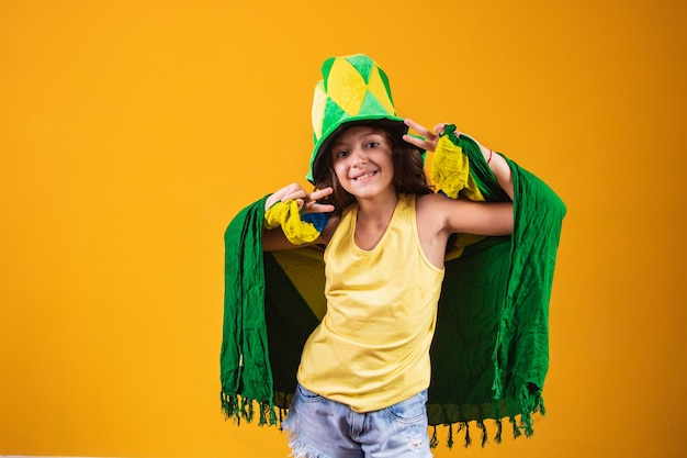 Torcedor de futebol, seleção brasileira. linda garotinha torcendo por seu time em fundo amarelo