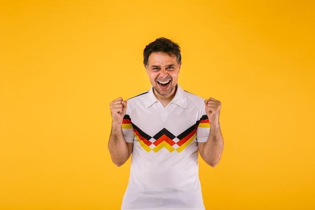 Torcedor de futebol vestindo uma camiseta branca com listras pretas, vermelhas e amarelas, aperta os braços animadamente e grita