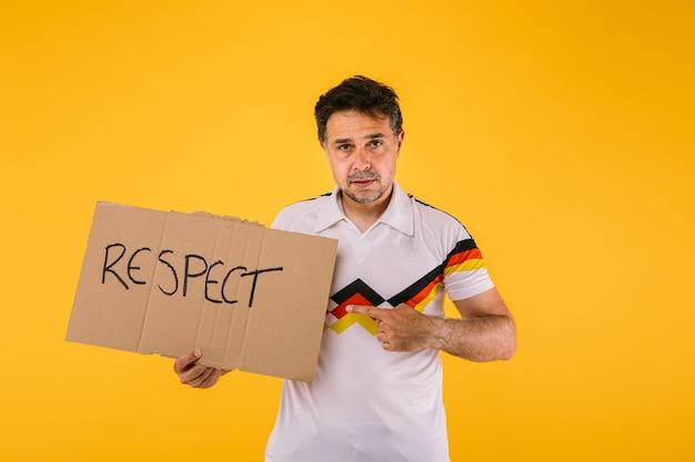 Torcedor de futebol vestindo uma camiseta branca com listras pretas, vermelhas e amarelas, segura uma placa que diz 'respeito'