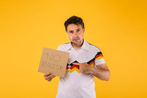 Torcedor de futebol vestindo uma camiseta branca com listras pretas, vermelhas e amarelas, segura uma placa que diz 'sem racismo'