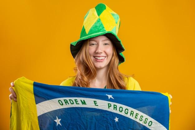 Torcedor do brasil. fã de mulher ruiva brasileira comemorando no futebol, jogo de futebol, cores do brasil. vestindo uma camiseta, bandeira e chapéu de fã.