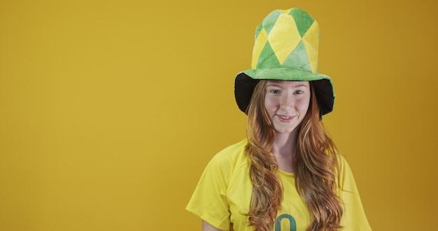 Torcedor do brasil. fã de mulher ruiva brasileira comemorando no futebol, jogo de futebol em fundo amarelo. cores do brasil. vestindo uma t-shirt, bandeira e chapéu de leque.