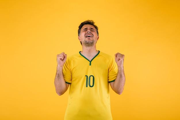 Torcedor do futebol brasileiro com a camisa amarela cerra os punhos e grita torcendo pelo time.