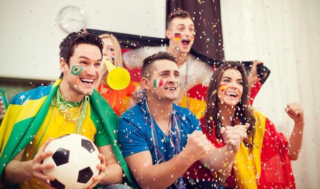 Torcedores multinacionais do futebol comemorando gol