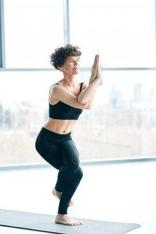 Torcendo a pose de ioga. mulher flexível no colchonete fazendo ioga ao lado de uma grande janela