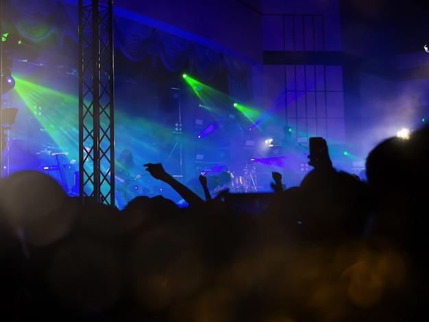 Torcendo fãs levantando suas mãos na batida em um concerto ao vivo grátis no festival de música.