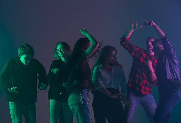 Torcendo festa de dança, conceito de desempenho. uma multidão de pessoas dançando com luzes coloridas de néon levantando as mãos na parede escura