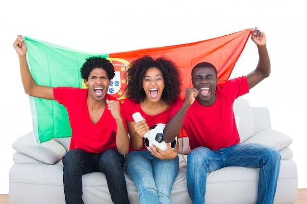Torcendo os fãs de futebol em vermelho sentado no sofá com a bandeira de portugal