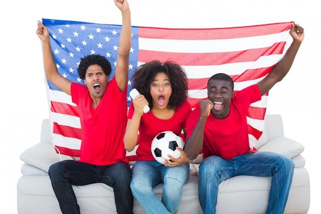 Torcer fãs de futebol em vermelho sentado no sofá com a bandeira do eua em fundo branco