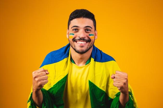 Torcida brasileira torcendo no meio da multidão em fundo amarelo.