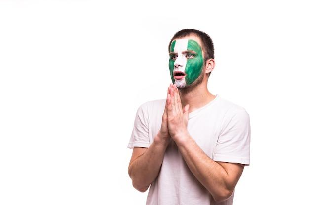 Torcida torcida da seleção da nigéria reza com o rosto pintado isolado no fundo branco