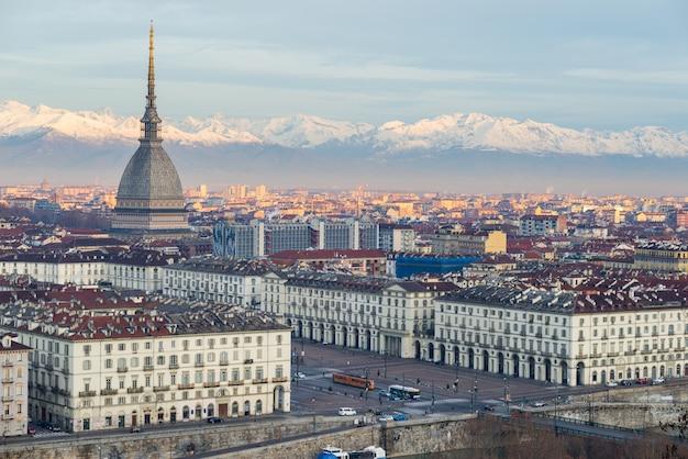 Torino (turim, itália): paisagem urbana ao nascer do sol com detalhes da toupeira antonelliana, elevando-se sobre a cidade.
