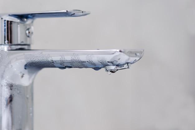 Torneira com uma gota de água em um fundo cinza. conceito de desligamento de água quente.
