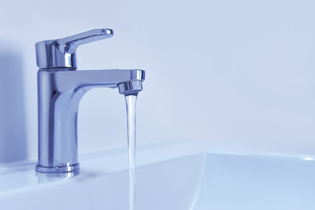 Torneira cromada brilhante com água corrente.