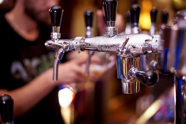 Torneira da cerveja com close-up das gotas em uma cerveja de derramamento borrada do barman do fundo em um vidro.