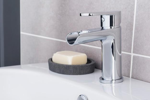 Torneira de aço nova e moderna com pia de cerâmica no banheiro