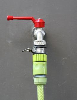 Torneira de água com tubo de borracha verde na parede cinza