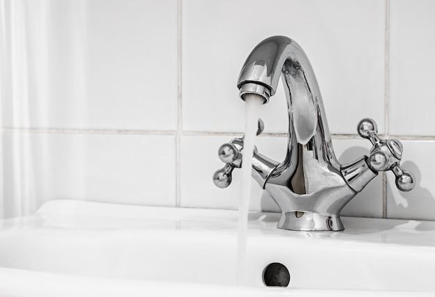 Torneira de água com um fluxo de água no banheiro