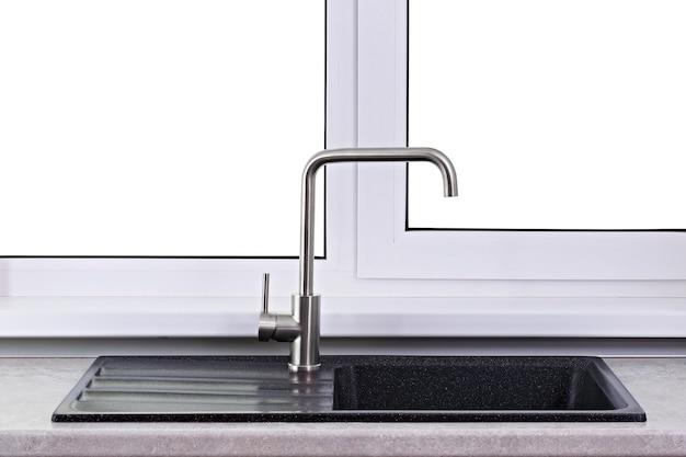 Torneira de água na cozinha com pia montada ao lado da janela