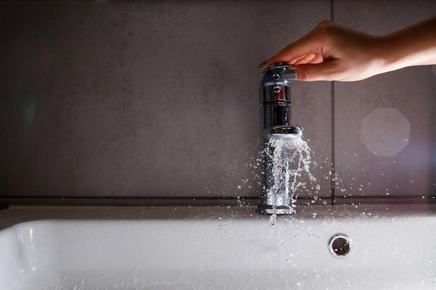 Torneira de água quebrada na pia do banheiro. salpicos de água da torneira prateada. foco seletivo