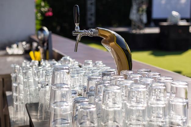 Torneira de cerveja e copos limpos no bar à luz do dia