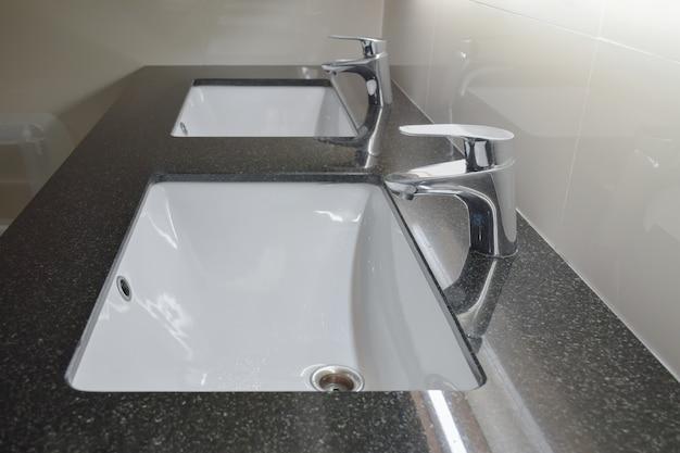 Torneira de estilo moderno com lavatório contrário no banheiro