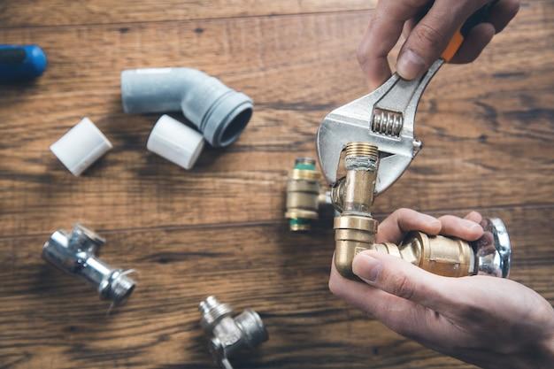 Torneira de mão de homem trabalhador com ferramentas na mesa