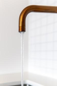 Torneira de metal com água corrente no fundo branco da parede da cozinha