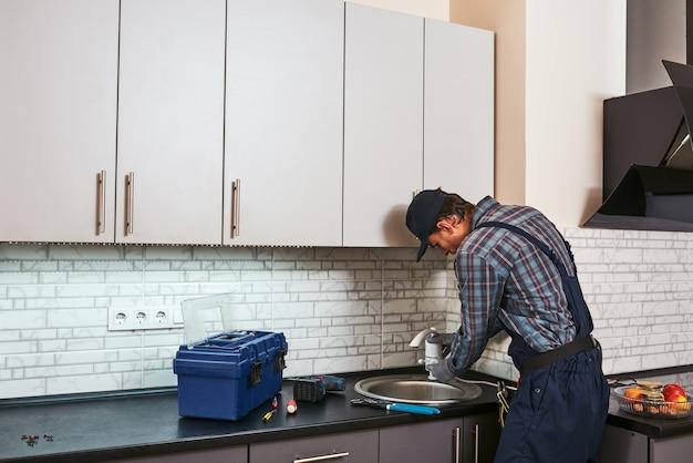 Torneira elétrica configurando vista traseira encanador bonito consertando pia na cozinha