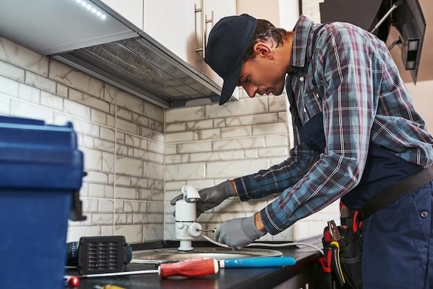 Torneira elétrica retrovisora encanador bonito consertando pia na cozinha