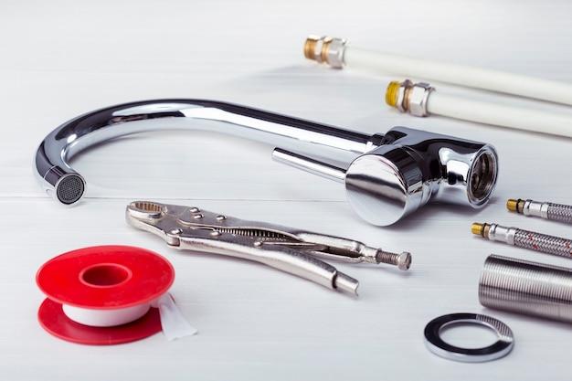 Torneira, ferramentas e equipamentos para encanador em um banheiro. material de encanamento no título branco.