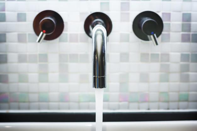 Torneira no banheiro com água corrente